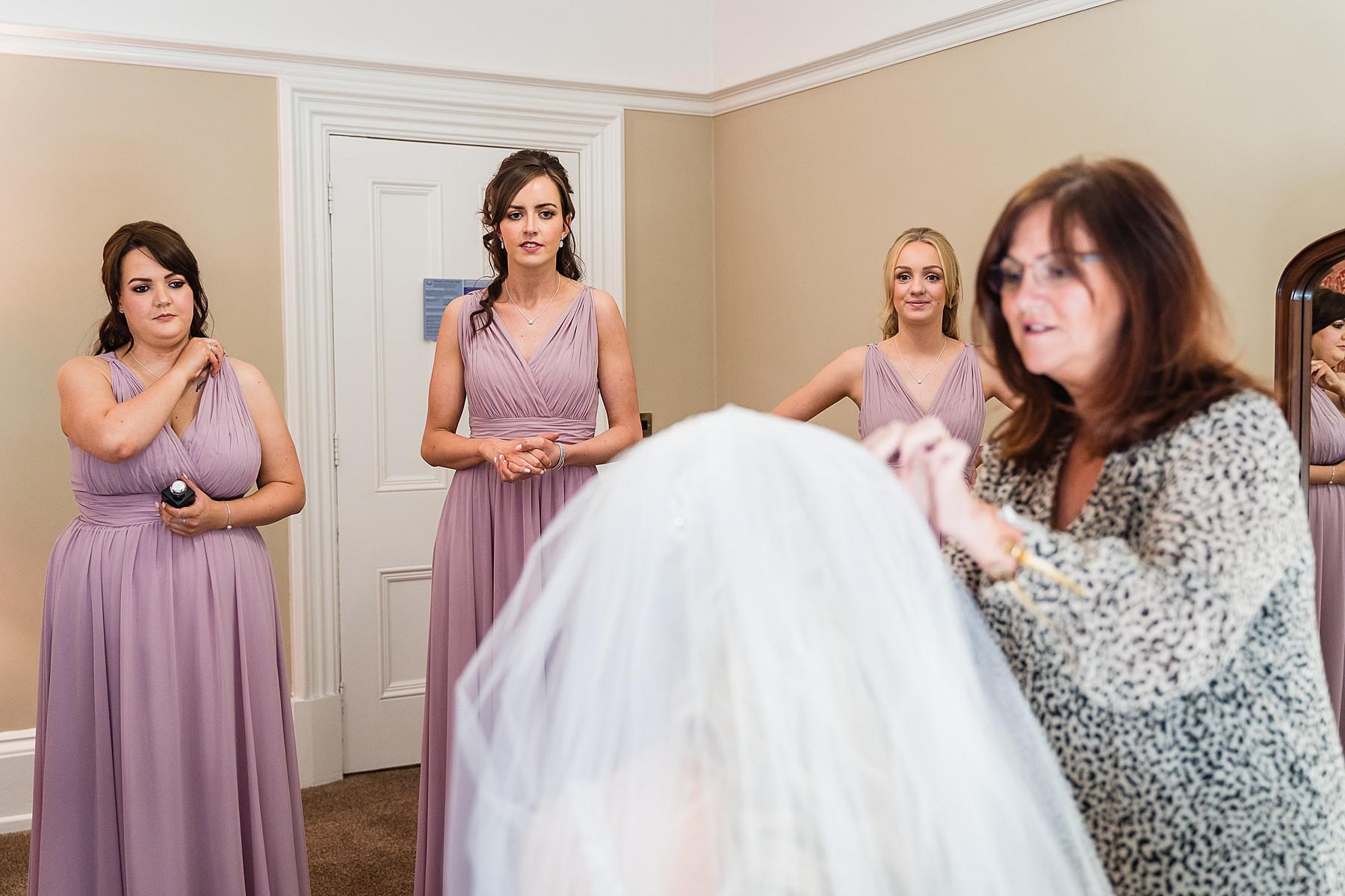 bridesmaids watching final preparations