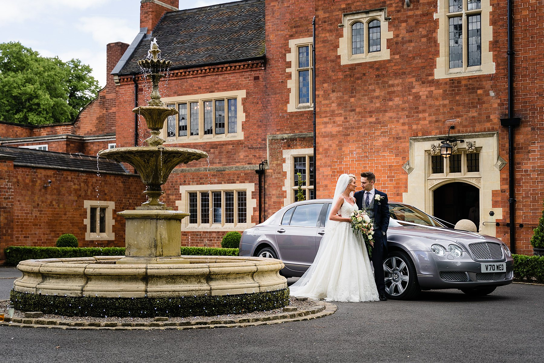 bride and groom posed shot with bentley