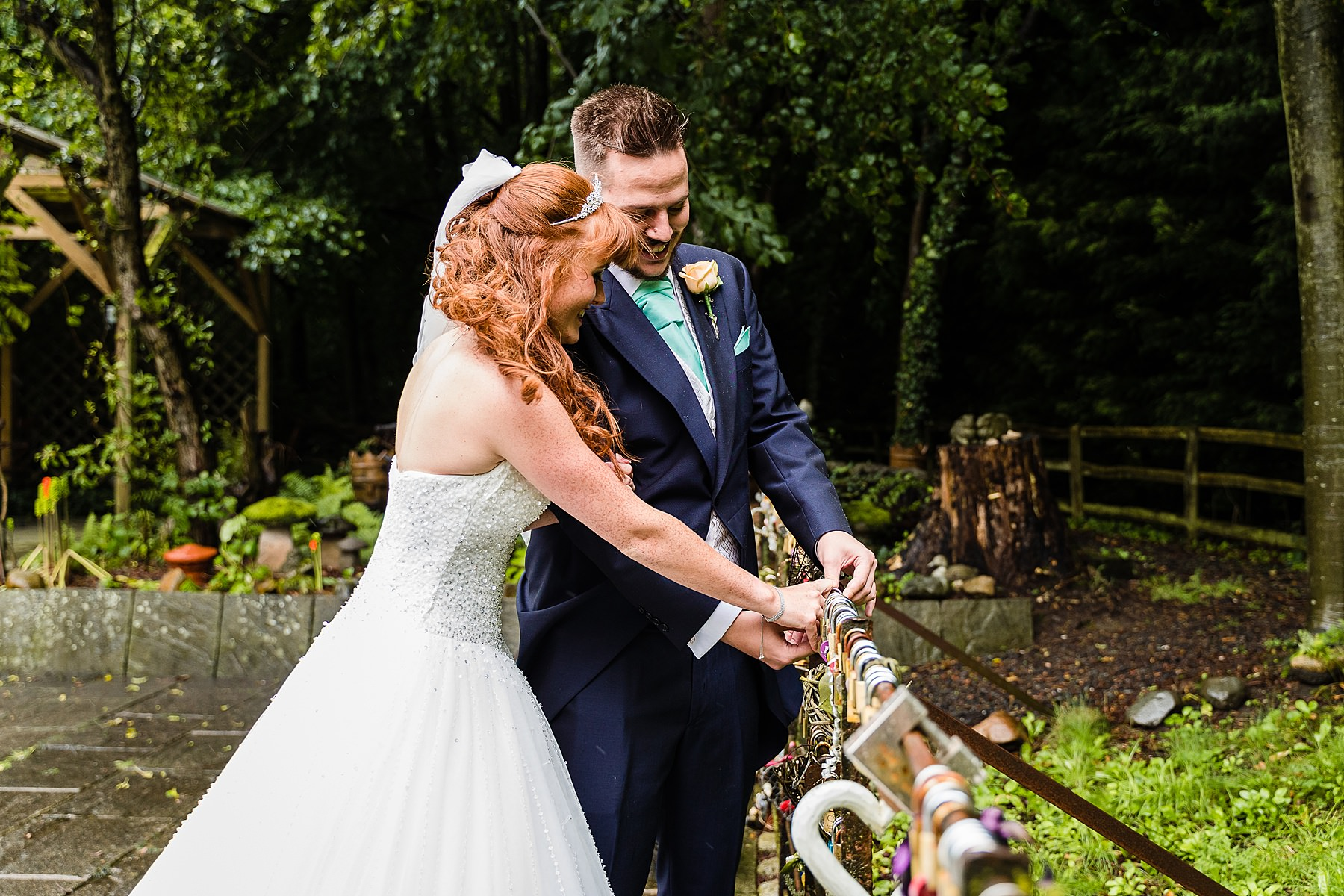 bride and groom attach lock at statham lodge