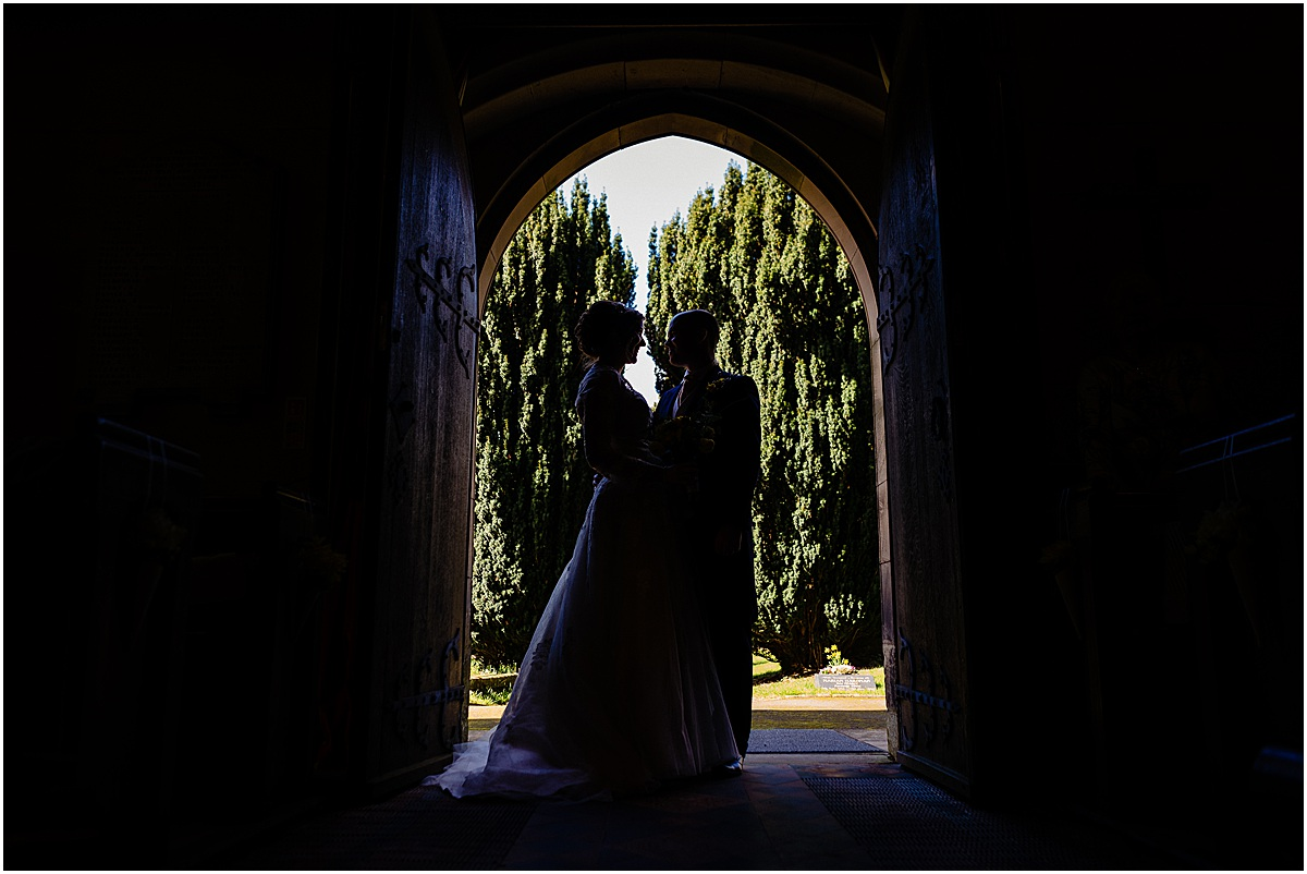 bride and groom in doorway of church