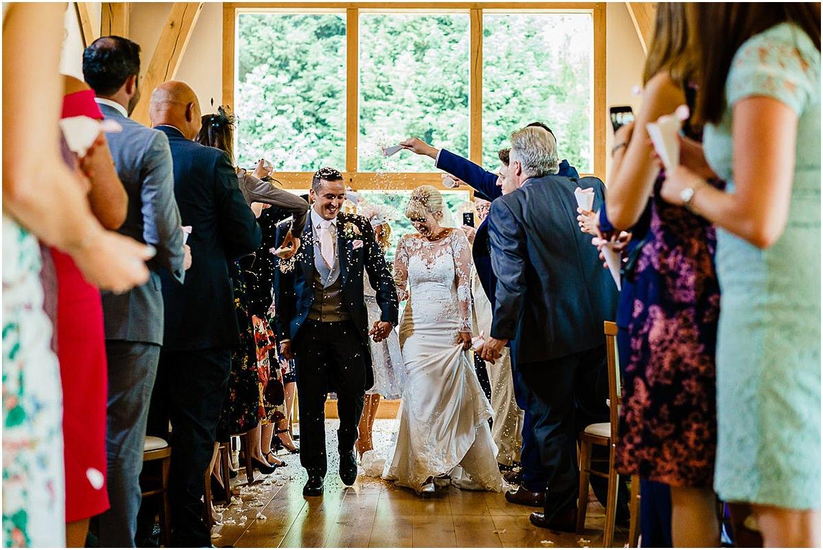 bride and groom walk down isle