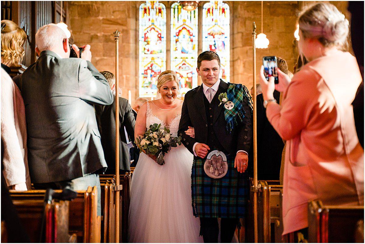 bride and groom walking down isle