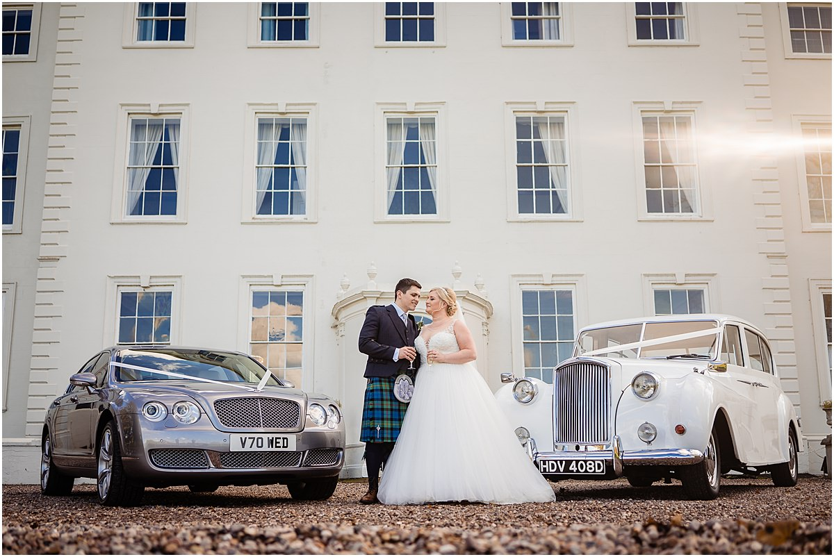 bride and groom with platinum wedding cars at somerford hall