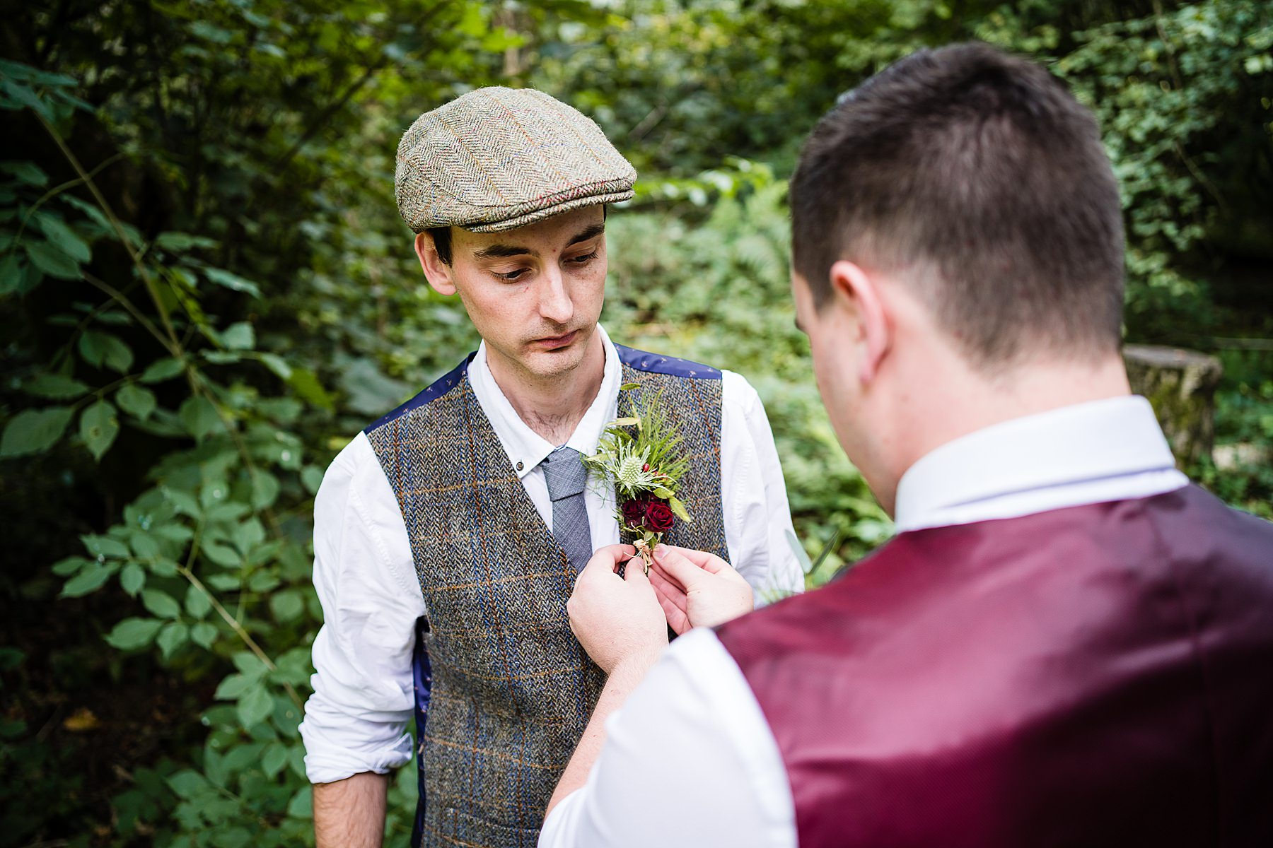 groom getting button hole attached